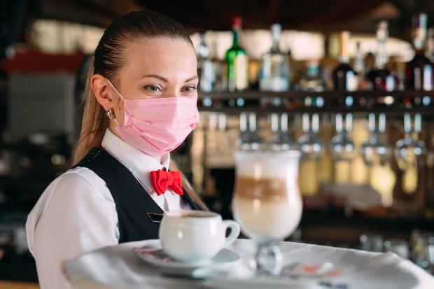 Junge Kellnerin mit rosafarbenem Mund-Nasen-Schutz