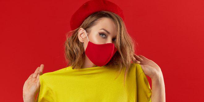 Junge modische Frau mit rotem Mund-Nasen-Schutz