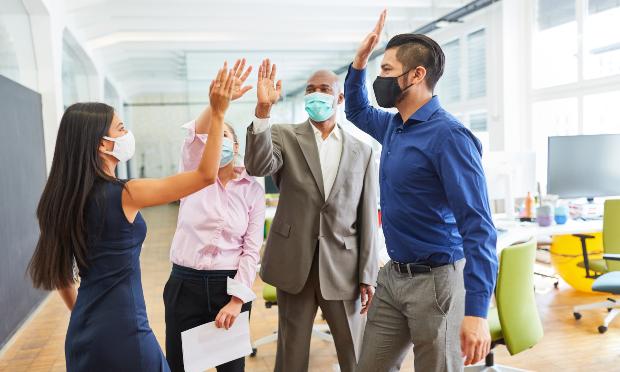 Gruppe junger Leute im Büro mit Mund-Nasen-Schutz