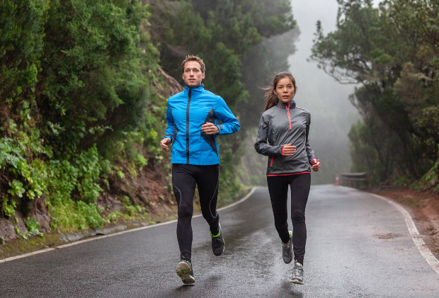 Ein junger Mann und eine junge Frau joggen bei Regenwetter durch einen Wald Die PU-Beschichtung bei Jacken