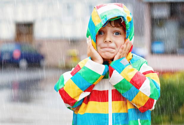 Ein kleiner Junge mit staunendem Gesichtsausdruck steht bei starkem Regen auf der Straße, seine Jacke bietet ihm offensichtlich guten Schutz Die PU-Beschichtung bei Jacken