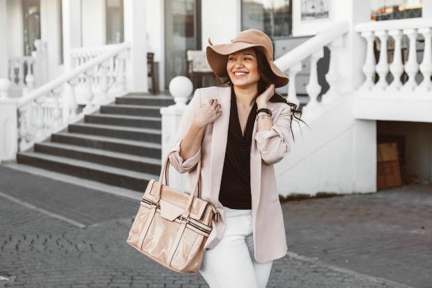Junge Dame in modischer Kleidung mut Hut und Täschchen