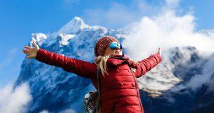 Frau in roter Jacke in den Alpen - Winterfarben Trends