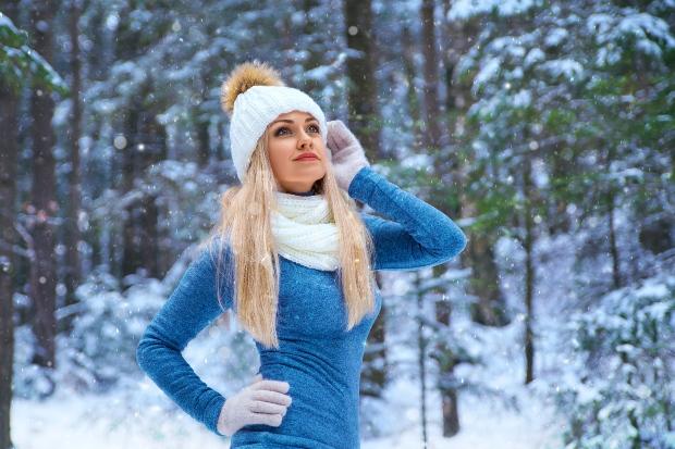 Frau steht mit blauem Winterpullover am Waldesrand