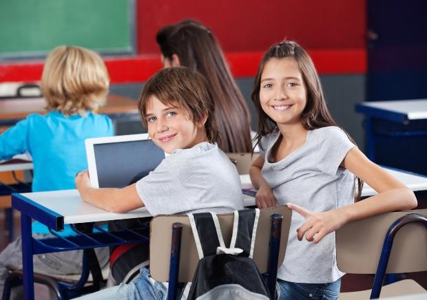 2 junge Schüler in der Schulklasse - ideale Schülerbekleidung ist oftmals schlicht
