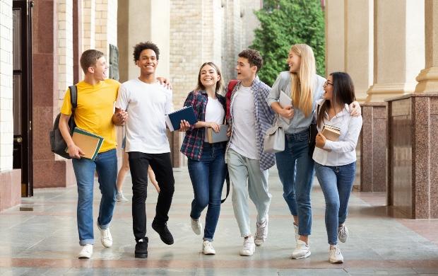 Studentengruppe am Campus - sie tragen Laptop-Rucksäcke