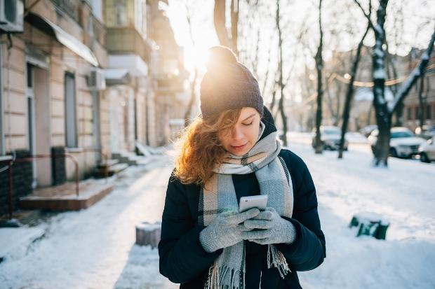 Junge Frau im Winter benutzt Handy mit Handschuhen