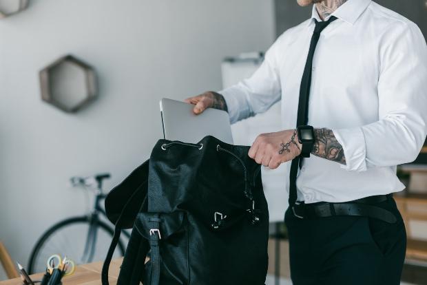 Junger Mann steckt Laptop in Laptop-Tasche