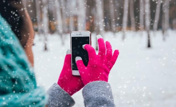 Junge Frau mit Handy und Touchscreen-Handschuhen