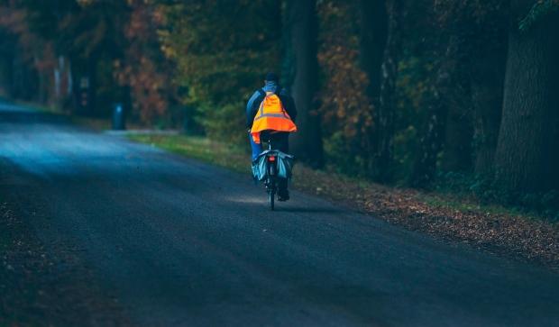 Mann auf Fahrrad bei Dunkelheit mit Sicherheitskleidung