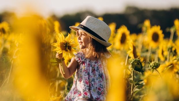 Kind mit Sommerkleid im Sonnenblumenfeld - Trends bei Kinderoutfits