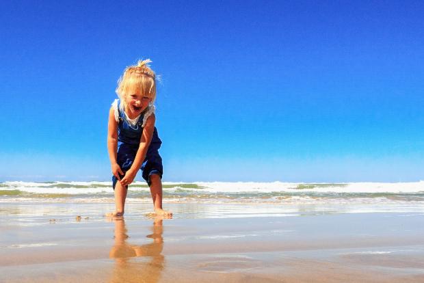 Mädchen mit blauer Latzhose am Strand